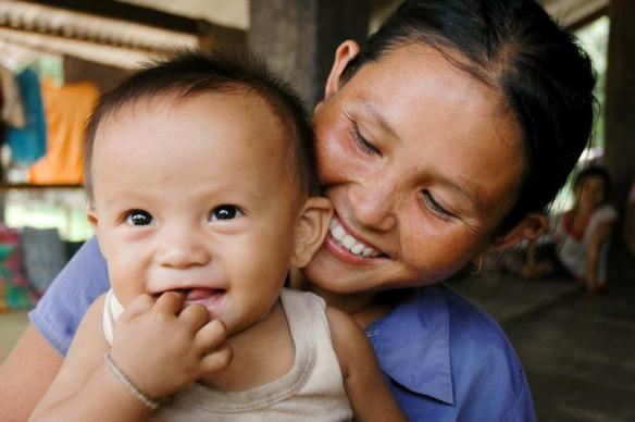 Mothers want their children to be happy and healthy. Mrs. Kham, 27 and Anoy, 8 months old. Her smile says it all. She has three young healthy children. World Vision has been working in the village of Phonthong in Pakkading District of Bolikhamxay Province in Lao PDR to provide health and education through the Pakkading Mother and Child Health Project (PMCH).